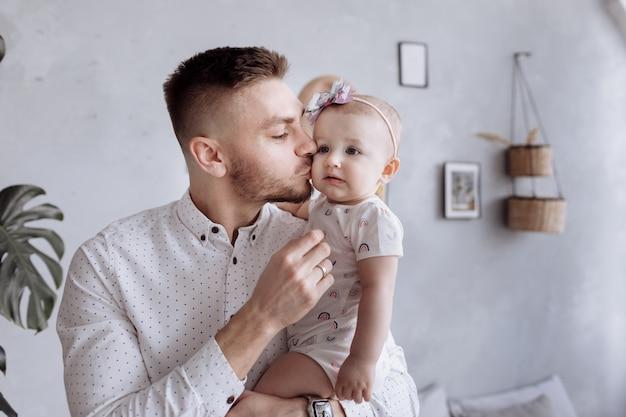 Папа целует и обнимает свою дочь. счастливая семья и день отца. Premium Фотографии