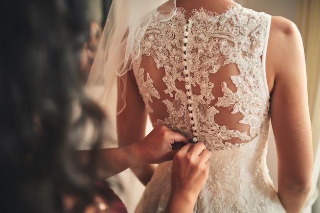 花嫁介添人花嫁のコルセットのクローズアップを締めます。結婚式の日。 Premium写真