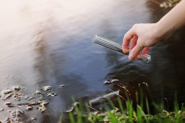 Ученый и биолог гидробиолог отбирает пробы воды для анализа на открытом воздухе. Premium Фотографии