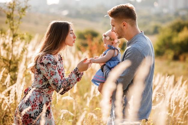 Мама, папа и маленькая девочка с удовольствием на открытом воздухе в траве в летний день. день матери, отца и ребенка. счастливая семья на прогулке. Premium Фотографии