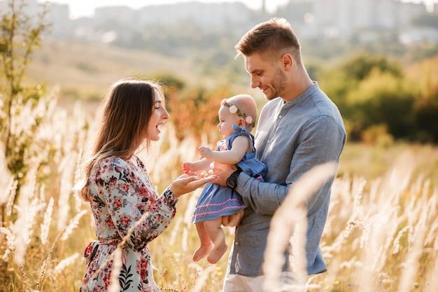 Мама, папа и маленькая женщина, весело на открытом воздухе в траве в летний день. день матери, отца и ребенка. счастливая семья на прогулке. Premium Фотографии
