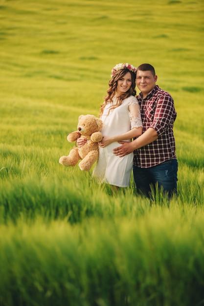 В ожидании малыша. родительства. беременная молодая женщина и ее муж с удовольствием держат в руках плюшевого мишку, выходя на улицу в поле зеленой травы. Premium Фотографии