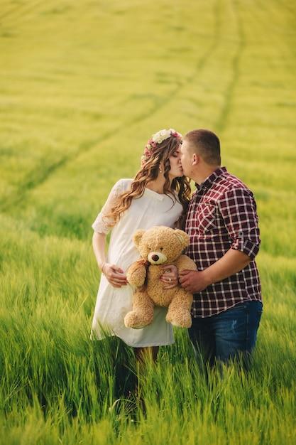 В ожидании малыша. родительства. беременная молодая женщина и ее муж счастливы поцеловать и держать плюшевого мишку в руках, идя в открытый в поле зеленой травы, избирательный подход. Premium Фотографии