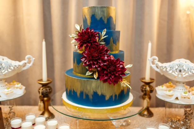 砂漠のお祝いテーブルの花の地位によって飾られた青いウエディングケーキ Premium写真