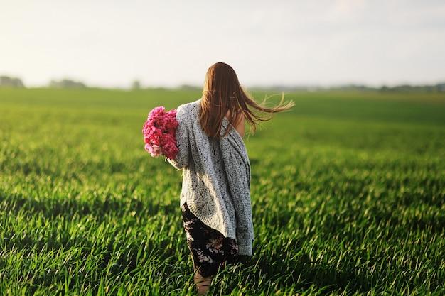 散歩、花の中の少女の美しい若い女性。牡丹のブーケ。ゴージャスな髪を持つエレガントな若い女性。牡丹を持つ少女が畑を歩きます。 Premium写真