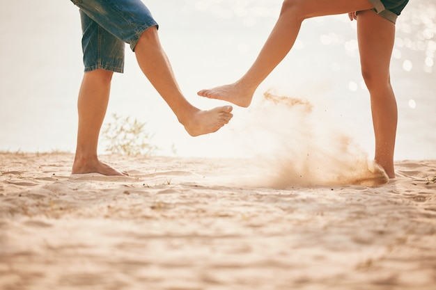 砂で遊ぶ若いカップル。夏のライフスタイル Premium写真