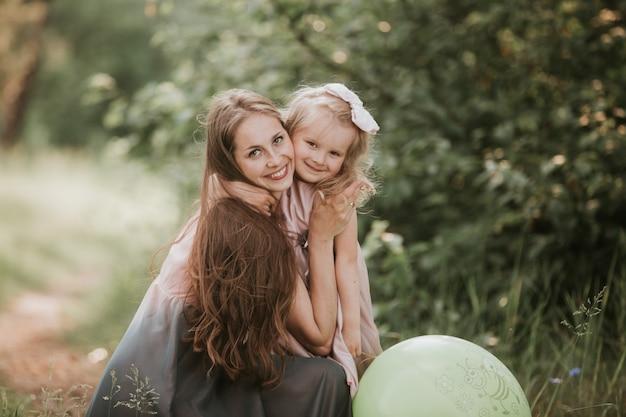美しい母親そして彼女の小さな娘は屋外で。自然。美の母と彼女の子供が一緒に公園で遊んでいます。幸せな家族の屋外のポートレート。母の日おめでとうございます。ママとベイビー Premium写真