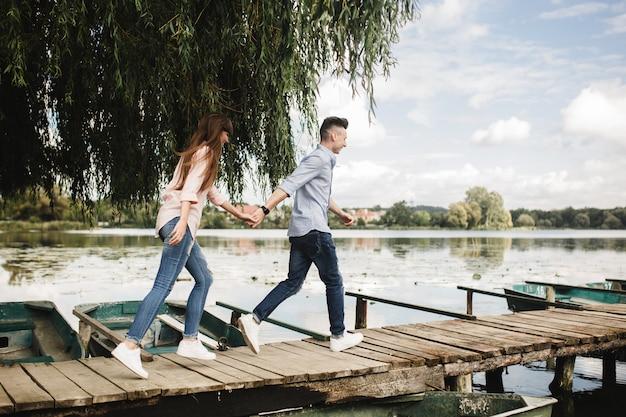 幸せな若いカップルは屋外。若い手を繋いでいる木製の橋に沿って実行しているカップルが大好きです。 Premium写真