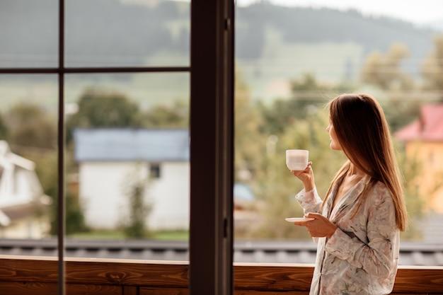 Женщина утром держит чашку чая или кофе и смотрит на горы, стоящие у окна Premium Фотографии