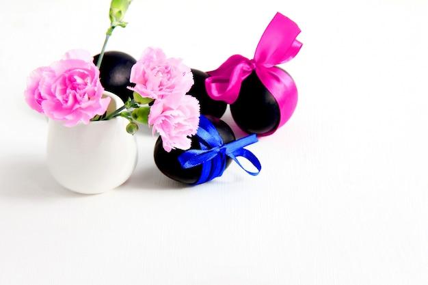 Черные пасхальные яйца и розовые цветы гвоздики на белом фоне Premium Фотографии