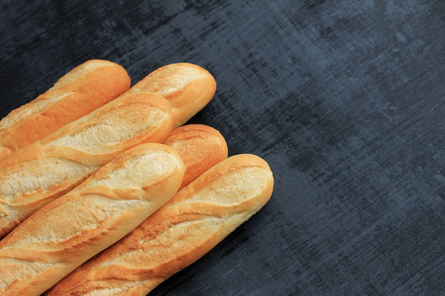 Французские багеты на черном фоне деревянные. Premium Фотографии