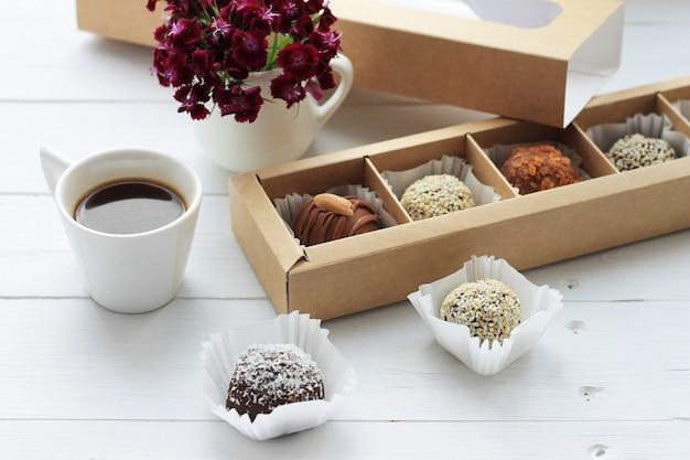 木製のテーブルにバレンタインデーのためのチョコレート菓子、一杯のコーヒーと花の束。 Premium写真