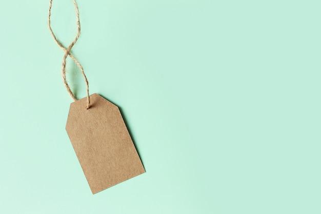 Ценник картона брайна на пастельном зеленом цвете, взгляд сверху. распродажа Premium Фотографии