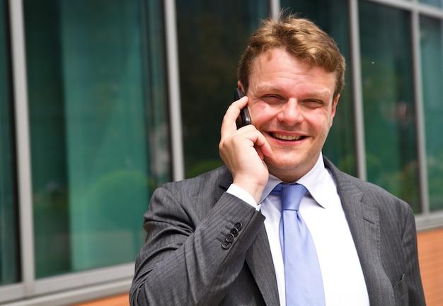 Портрет молодого бизнесмена, разговаривает по телефону Premium Фотографии