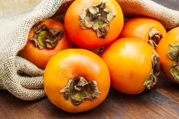 Вкусные свежие фрукты хурмы на деревянный стол Premium Фотографии
