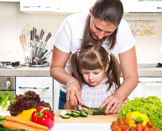 野菜を準備する台所で母と娘 Premium写真