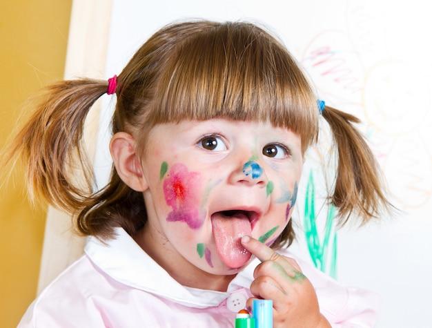 小さな女の子が塗料を描画します Premium写真