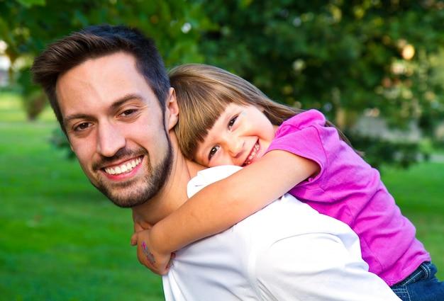 公園で彼女の兄弟の肩の上を歩く少女 Premium写真