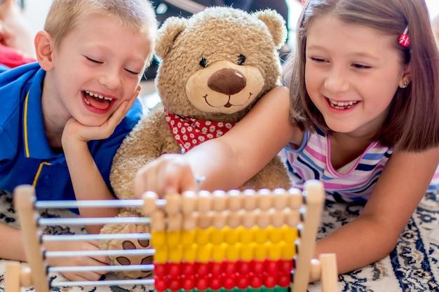 Маленькие дети играют со счетами дома Premium Фотографии