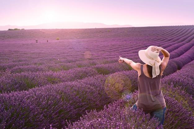 ピンクの夕日にラベンダー畑の女性 Premium写真