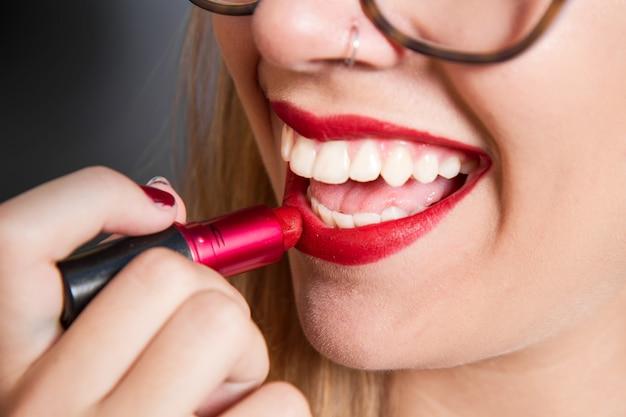 微笑んでいる女の子は唇に口紅を置く Premium写真
