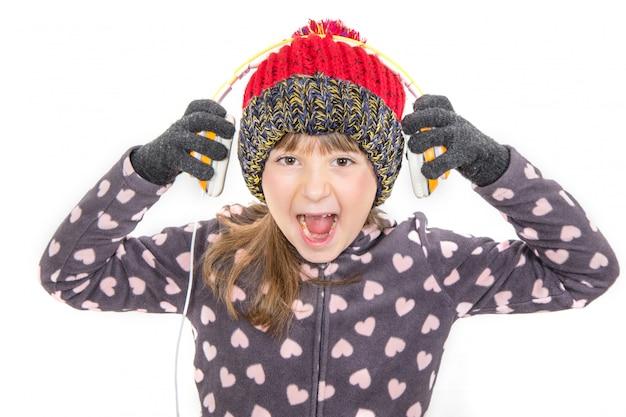 Молодая девушка в перчатках и шерстяной шапке слушает музыку в наушниках Premium Фотографии