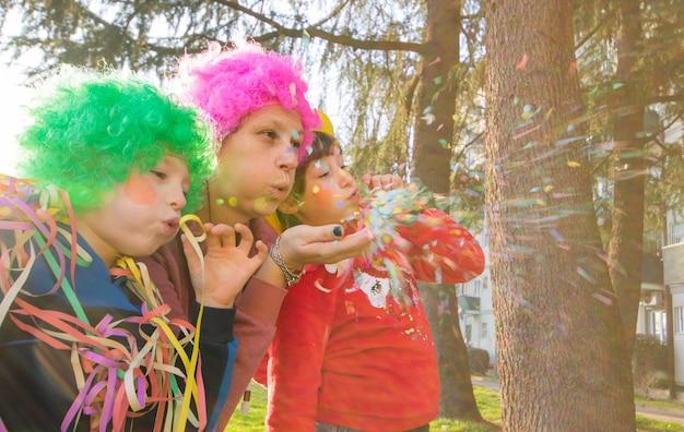 母と彼女の子供たちはカーニバルの衣装で紙吹雪で遊んでいます。 Premium写真
