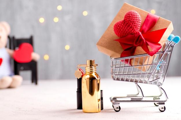 ショッピングカート、ギフト用の箱、ハート、口紅、香水の概念的な休日のイメージ Premium写真