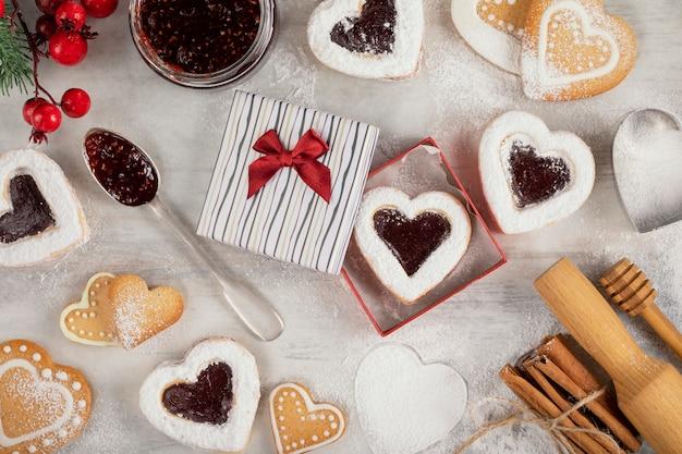 Домашнее печенье в форме сердца с малиновым вареньем на белом деревянном столе на рождество или день святого валентина. Premium Фотографии