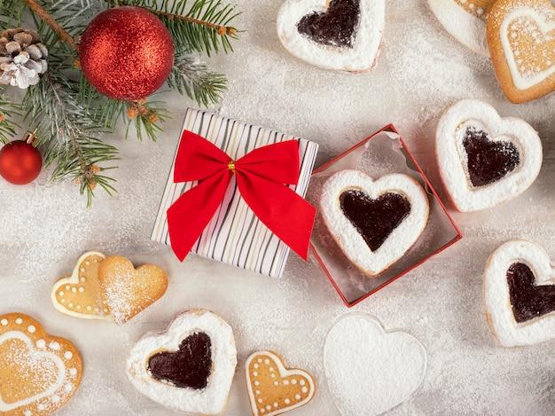 Домашнее печенье в форме сердца с малиновым вареньем на белом деревянном столе на рождество или день святого валентина. вид сверху. Premium Фотографии