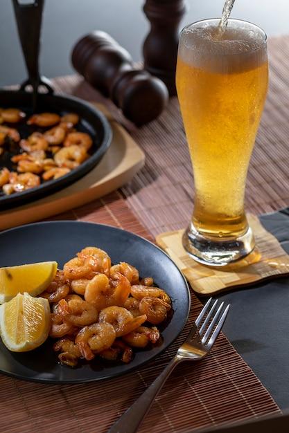 揚げ海老とレモンビールのグラスと黒のプレート Premium写真