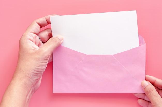 ピンクの背景にピンクの封筒で空白の白い挨拶の紙のカードを手に Premium写真