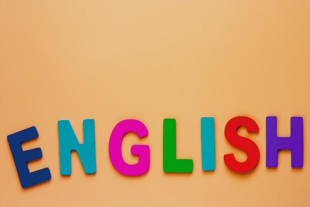 概念を学習するためのベージュ色の背景に木製の文字から英語の単語 Premium写真