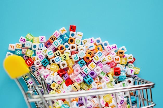 ミニショッピングカートまたはトロリーの青色の背景に英語の文字ビーズ Premium写真