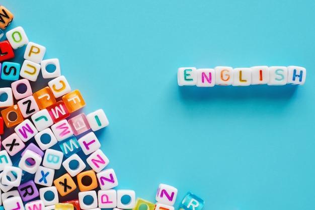 青色の背景に文字ビーズと英語の単語 Premium写真