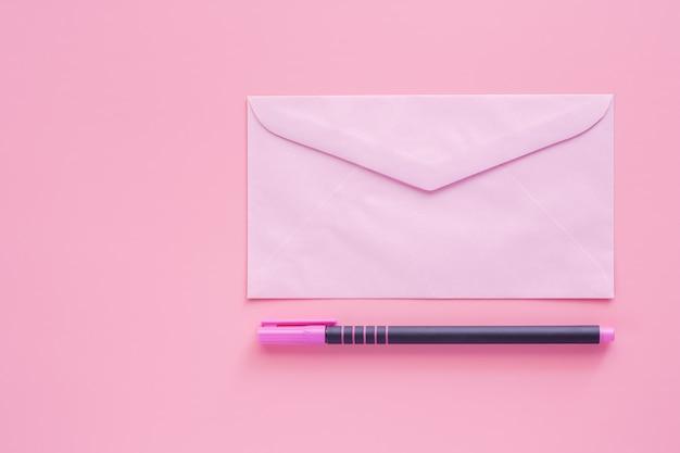 手紙や書類を囲むためのペンとピンクの封筒 Premium写真