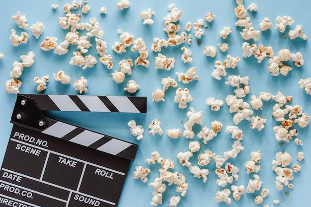 エンターテイメントの概念のための青のポップコーンと映画クラッパーボード Premium写真