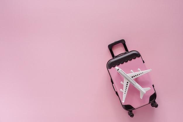 旅行と旅のためのピンクの背景に小指の荷物を持つ白い飛行機モデル Premium写真