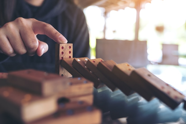 テーブルに落ちるから木製のドミノのゲームを停止しようとする手の拡大画像 Premium写真