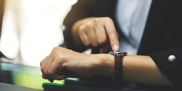 Деловая женщина, указывая на наручные часы на ее рабочее время, ожидая кого-то в офисе Premium Фотографии