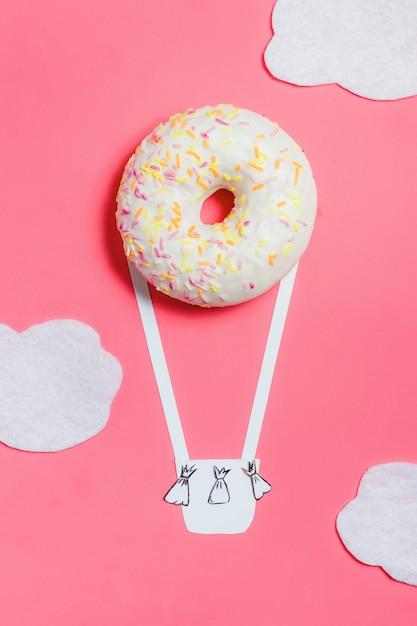 ピンクのドーナツ、創作料理のミニマリズム、雲と空のエアロスタットの形をしたドーナツ、コピースペース付きの平面図、トーン Premium写真