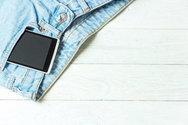 白い木製の背景にビンテージスタイルのポケット古いジーンズのスマートフォン Premium写真