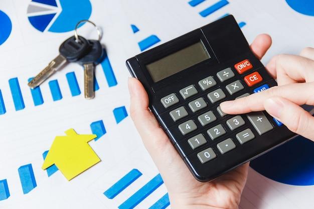 図で机の上の紙の家モデルと電卓を使用して女性の手のクローズアップ。 Premium写真