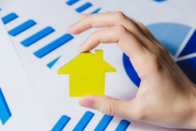 黄色い紙の家を保持している女性の手 Premium写真