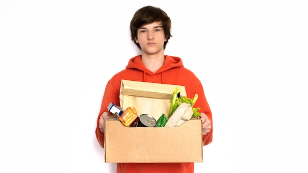 Бесконтактная доставка. человек в медицинской маске и перчатках держит коробку. Premium Фотографии