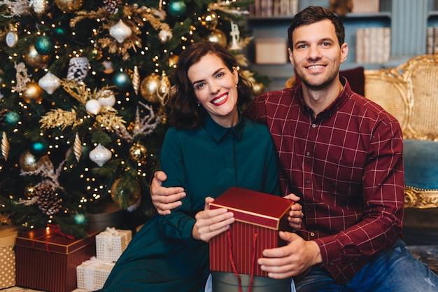 Счастливая восхитительная влюбленная пара, обнимаются, сидят возле украшенной новогодней елки, держат подарок Premium Фотографии