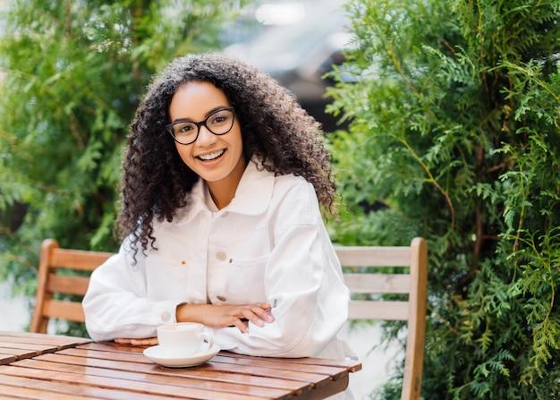 Афро женщина в белых одеждах, пьет кофе в кафе на открытом воздухе Premium Фотографии