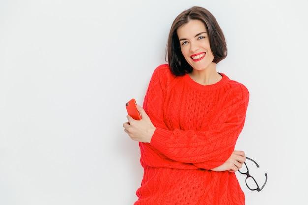 黒髪の格好良い笑顔ブルネットの女性、赤いニットのセーターを着て、メガネと現代のスマートフォンを保持 Premium写真