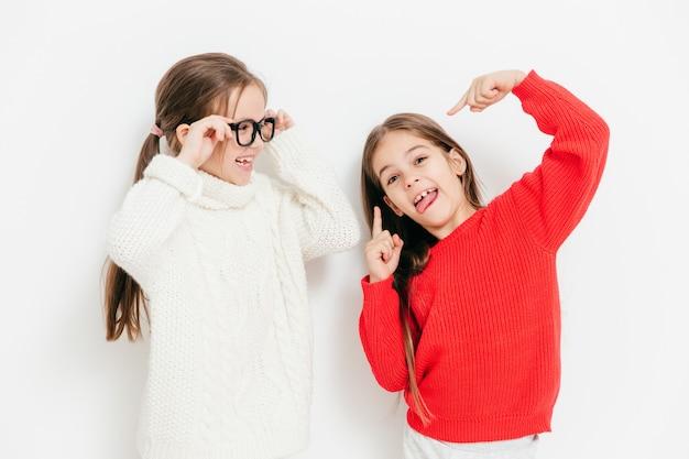 Веселые две сестры веселятся вместе, имеют смешные выражения Premium Фотографии