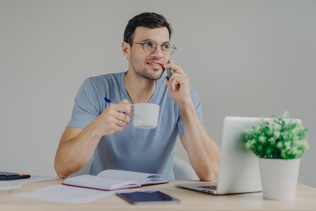 丸いメガネで楽しい探している男性会計士は、熱い飲み物をすすり、モバイル会話をしています Premium写真